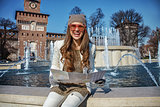 smiling modern tourist woman in Milan, Italy with map