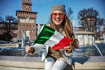 tourist woman near Sforza Castle in Milan, Italy showing flag