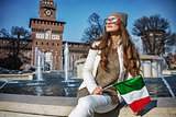 traveller woman near Sforza Castle in Milan with Italian flag