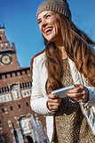smiling young traveller woman in Milan, Italy writing sms