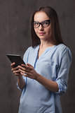 portrait of beautiful happy young woman with glasses reading eBook