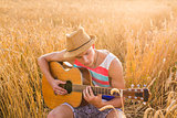 Happy handsome man is playing guitar in the field
