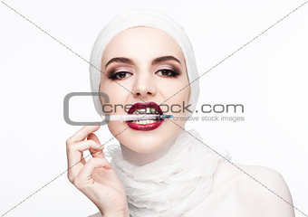 Beautiful model holding syringe in lips surgery