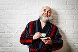 Happy Senior Man with Beard Drinking Coffee