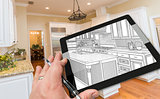 Hand on Computer Tablet Showing Drawing of Kitchen Photo Behind