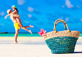 colourful straw beach bag abd hugging honeymoon couple on background