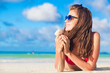 beautiful long haired woman sunbathing at the beach