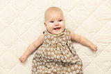 happy smiling baby girl on blanket in bed