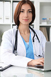 Happy brunette female doctor sitting at the table and filling up medical history form