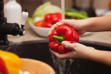 Making a vegetables salad, washing ingredients - red bell pepper