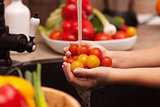 Making a vegetables salad, washing ingredients - cherry tomatoes
