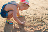 Cute little girl playing with sand on the beach
