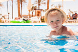 Cute happy little girl having fun in swimming pool