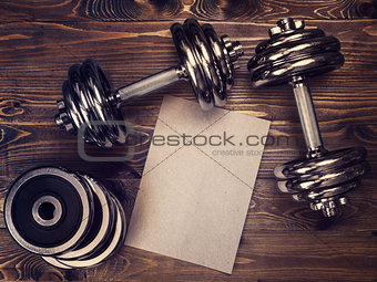 Toned image of metal dumbbells and a sheet of craft paper
