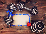 Toned image of metal dumbbells, blue atlas ribbon, red heart and a sheet of craft paper