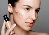 Beauty fashion model woman holding foundation tube