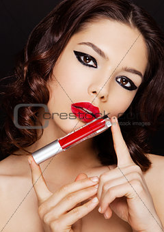 Beautiful model girl holding liquid red lipstick