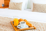 tray with healthy breakfast in bed in the hotel room