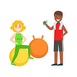 Woman Doing Exercise On Ball WIth Help Of Personal Trainer, Member Of The Fitness Club Working Out And Exercising In Trendy Sportswear