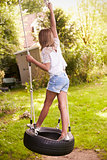 Rear View Of Young Girl Playing On Tire Swing In Garden