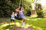 Brother Pushing Sister On Tire Swing In Garden