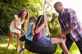 Parents Pushing Children On Tire Swing In Garden