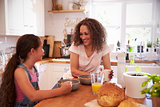Mother And Daughter Eating Breakfast In Kitchen Together