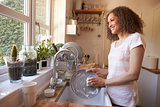 Woman Standing At Kitchen Sink Washing Up