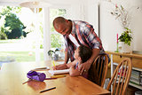 Father Helping Daughter With Homework At Table