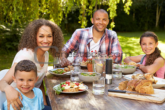 Portrait Of Family At Home Eating Outdoor Meal In Garden