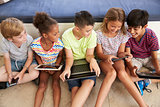 Overhead Shot Of Children Sitting On Floor Using Technology