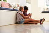 Two Children Sitting On Floor And Playing With Smartphone