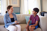 Young Boy Talking With Counselor At Home