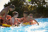 Children Having Fun On Inflatable In Outdoor Swimming Pool