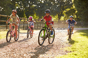 Four Children On Cycle Ride In Countryside Together