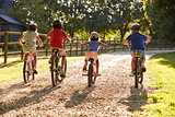 Rear View Of Children On Cycle Ride In Countryside Together