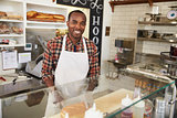 Man behind the counter at a sandwich bar looking to camera