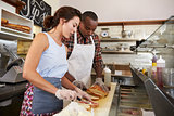 Couple preparing sandwiches at a sandwich bar counter
