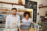 Mixed race couple behind counter at sandwich bar, close up