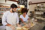 Mixed race couple work behind the counter at a sandwich bar