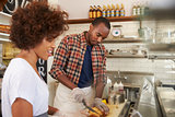 Black couple prepare food behind counter at a sandwich bar
