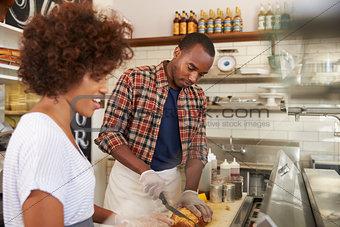 Black couple prepare food behind counter at a sandwich bar