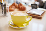 Large cappuccino coffee in yellow cup and saucer on counter