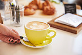 WomanÕs hand and cappuccino coffee in yellow cup and saucer