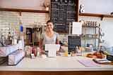 Woman ready to serve behind the counter at a coffee shop