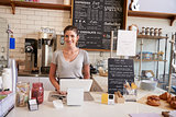 Woman waiting behind the counter at a coffee shop, close up