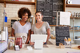 Two women behind the counter at a coffee shop, close up