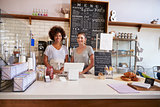 Two women ready to serve behind the counter at a coffee shop