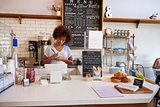 Waitress writing down an order at the counter of coffee shop