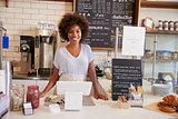 Smiling waitress behind counter at a coffee shop, close up